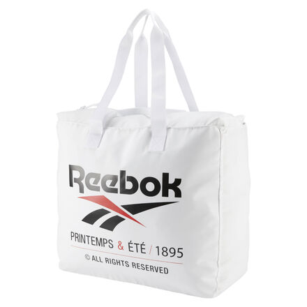 Reebok celebrates its century-plus years of history with a brand graphic across this tote bag. Made of durable polyester material, this roomy bag fits plenty of stuff. An inner zip pocket help you keep track of small items. 100% polyester 19.5\